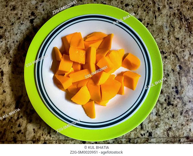 Fresh mango in a colorful bowl sitting on a granite counter