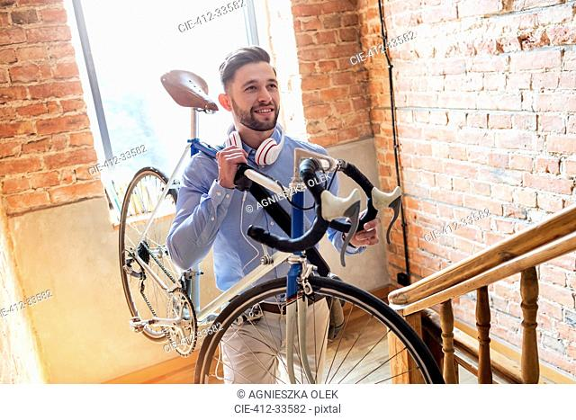 Man carrying bicycle up brick stairway