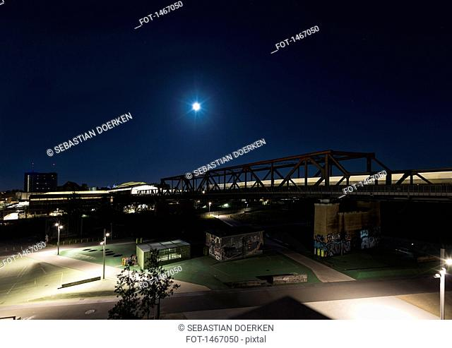 Bridge over illuminated city streets at night