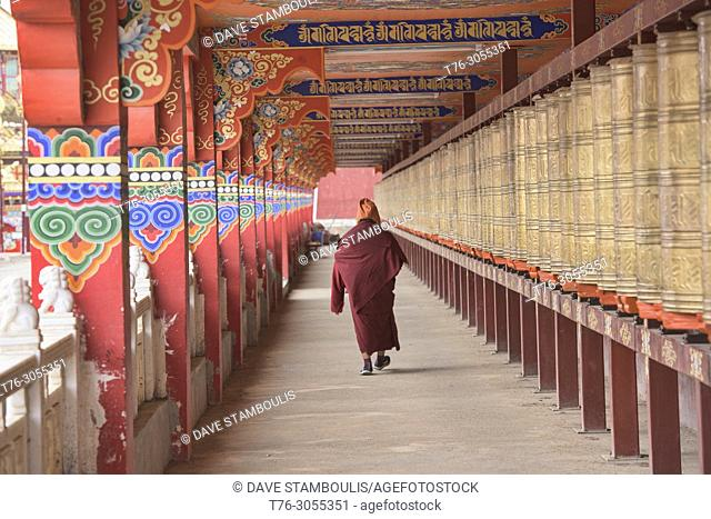 Tibetan monk spinning prayer wheels, Yarchen Gar, Sichuan, China