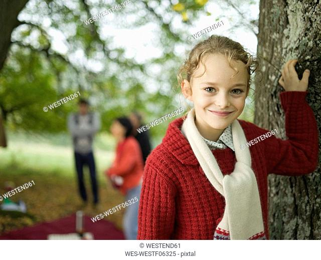Germany, Baden-Württemberg, Swabian mountains, girl leaning on tree, people in background