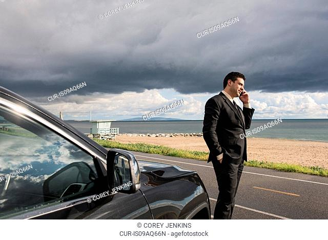 Businessman talking on smartphone at coastal parking lot