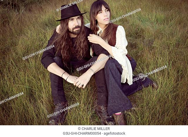 Bohemian Couple Sitting in Tall Grass, Close-Up
