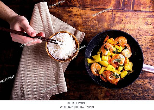 Frying pan of prawns with pineapple and man's hand taking rice with chopsticks