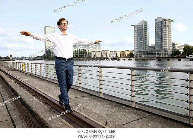 Germany, Berlin, businessman balancing on a rail at River Spree
