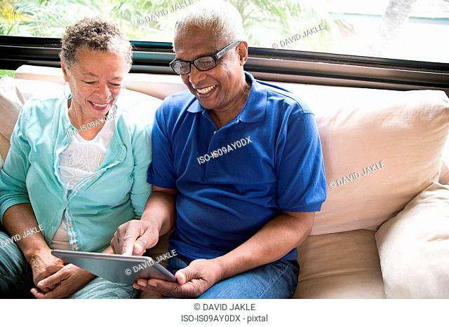 Senior couple sitting on sofa, using digital tablet