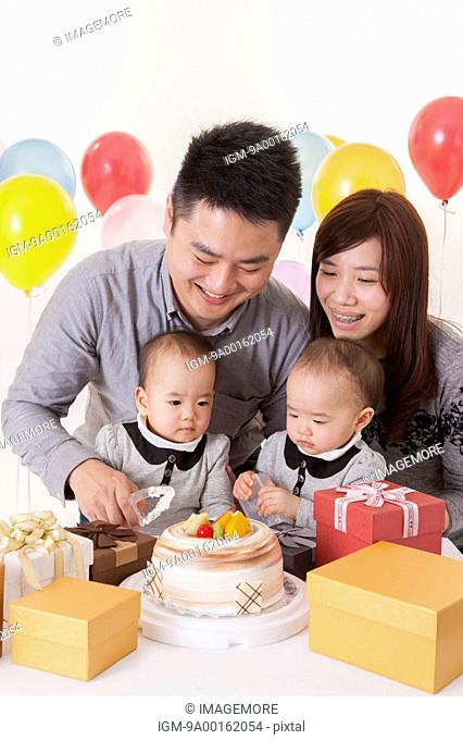 Young family with baby twins and celebrating birthday together