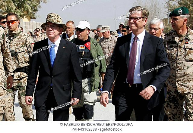 German Defence Minister Thomas de Maiziere (centre L) and German Foreign Minister Guido Westerwelle (centre R) arrive at the handover ceremony of a German base...