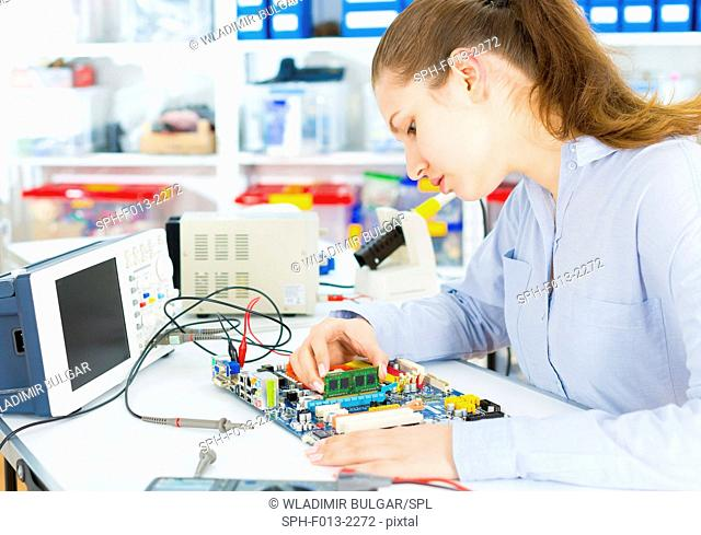 Female electrical engineer working on a circuit board
