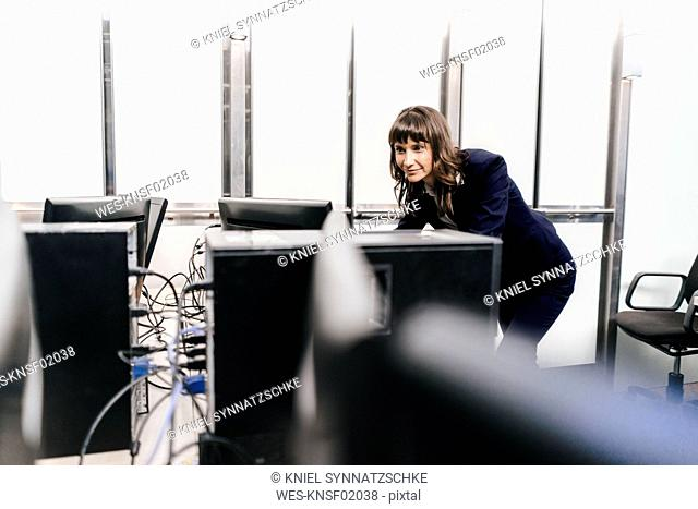 Successful businesswoman looking at monitors in office