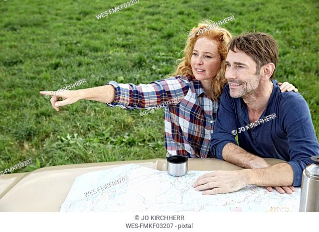 Couple at pick up truck with map with woman pointing