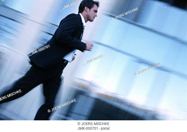 A salesman, businessman, tradesman, employee, officer, young man on the run in front of an office building
