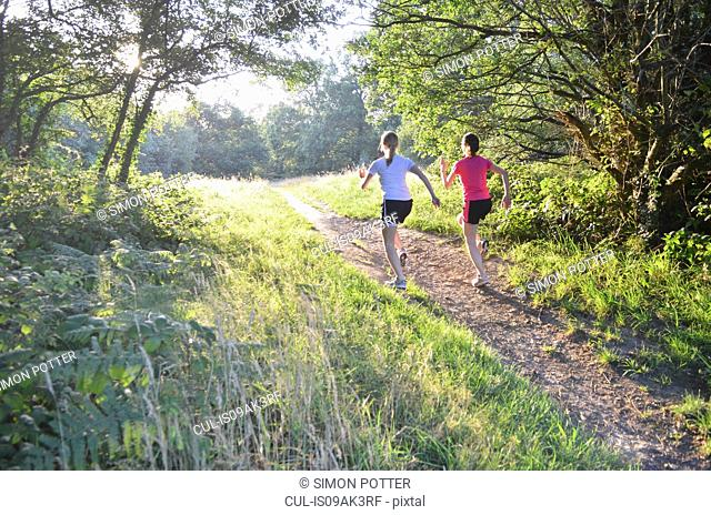 Two young women runners running up forest track in morning