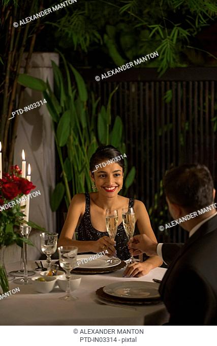 Singapore, Man and woman drinking champagne at romantic dinner
