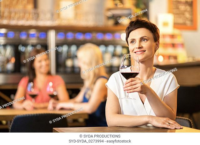 happy woman drinking red wine at bar or restaurant
