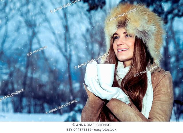 Portrait of a beautiful young girl wears a stylish hat standing in a snowy park and warming hands on a hot mug of tea, enjoying the beautiful winter view