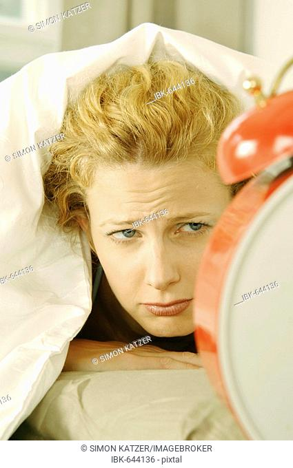 Woman laying in bed, looking at alarm clock