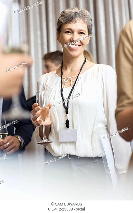 Portrait of smiling mature businesswoman holding champagne flute