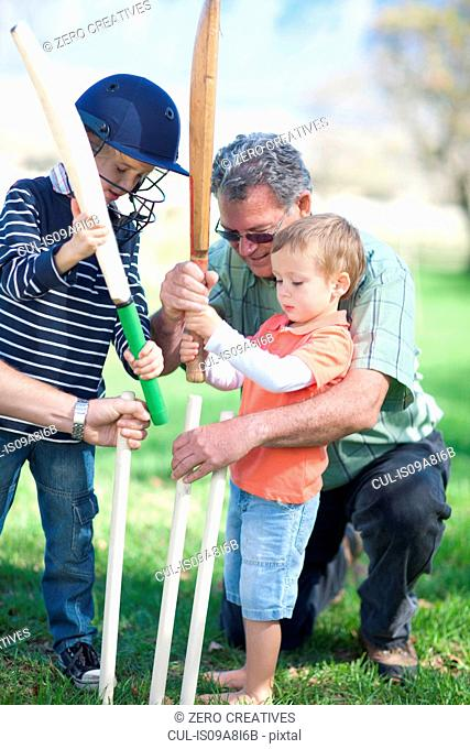 Boys and grandfather preparing stumps for cricket
