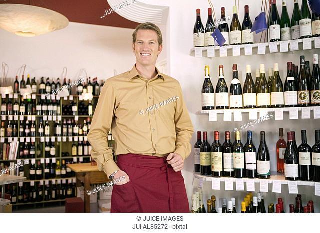 Wine shop clerk smiling next to shelves of wine bottles