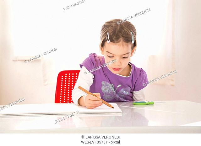 Little girl making a drawing on sheet of paper