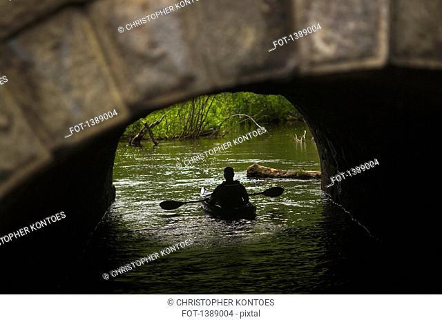 Rear view of man rowing boat under arch bridge