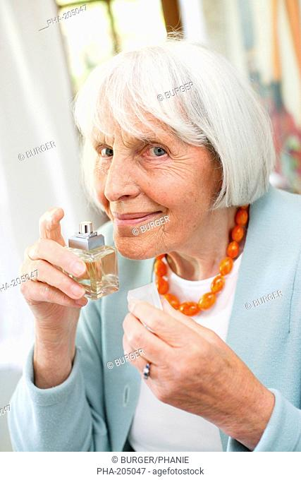 80 years old woman putting perfume on