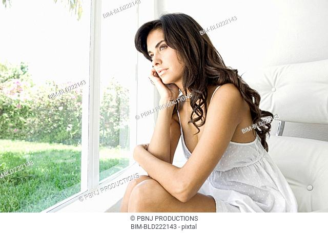 Hispanic woman looking out window