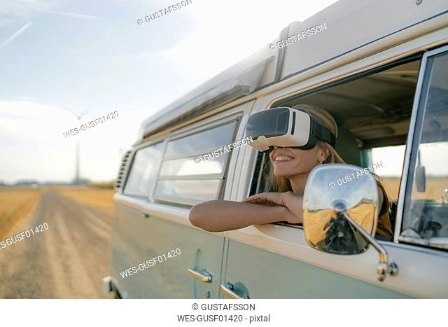 Smiling woman wearing VR glasses leaning out of window of a camper van