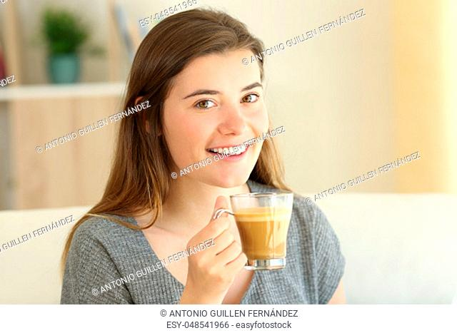 Portrait of a happy teen holding a coffee with milk cup looking at camera sitting on a couch in the living room at home