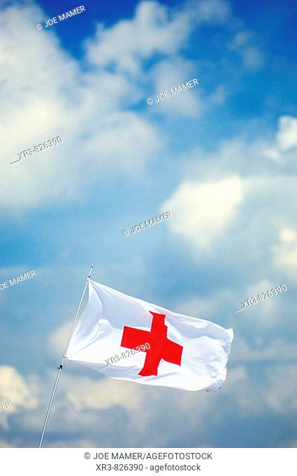 Red Cross flag blowing in wind against blue sky and clouds