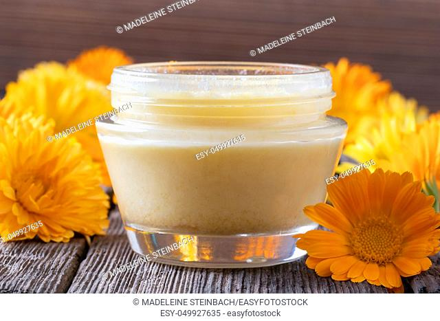 A jar of homemade ointment made from shea butter and fresh calendula flowers