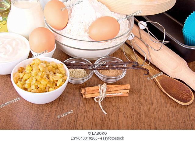 Flour, milk, sour cream and eggs, raisin, sesame, vanilla and cinnamon on a table