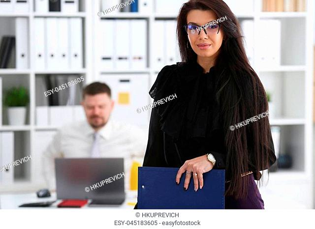Beautiful smiling brunette woman hold in arms pink pen and paper clipped to pad wearing stylish glasses portrait. White collar worker at workspace officer...