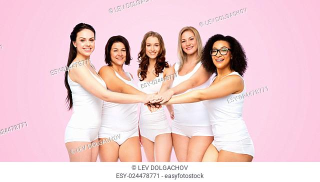 gesture, friendship, beauty, body positive and people concept - group of happy different women in white underwear holding hands together on top over pink...