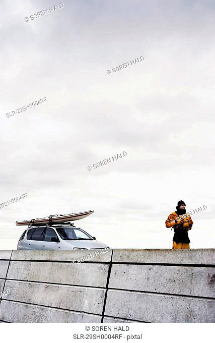 Man in front of car with kayak