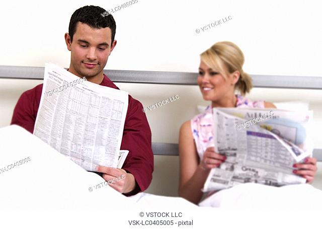 Couple in bed reading newspaper