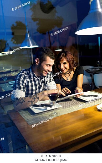 Young couple in modern restaurant with digital tablet at evening twilight