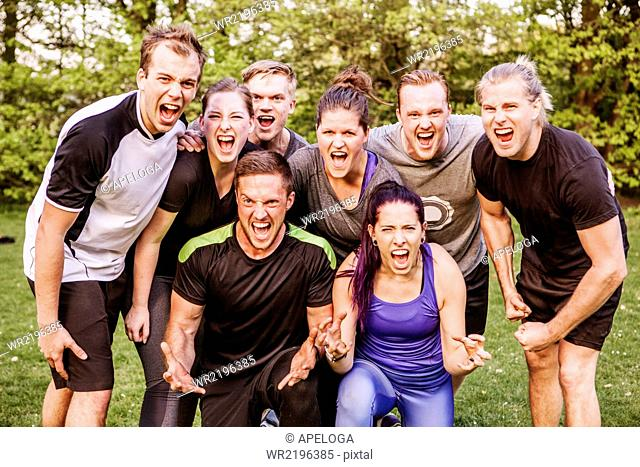 Group portrait of male and female friends screaming in park