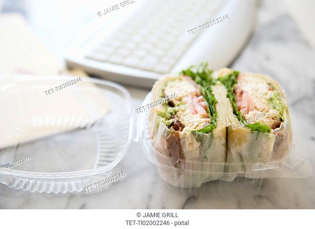 Studio shot of sandwich in box and computer keyboard
