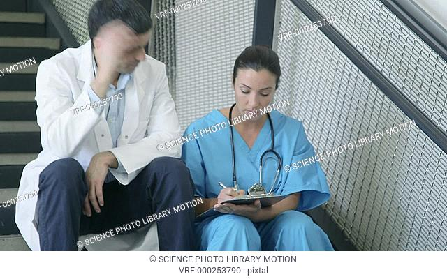 Male and female doctors sitting on staircase with medical notes