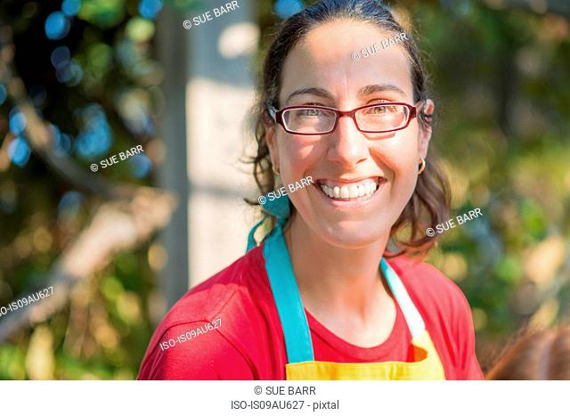 Portrait of mature woman wearing apron and glasses looking at camera smiling