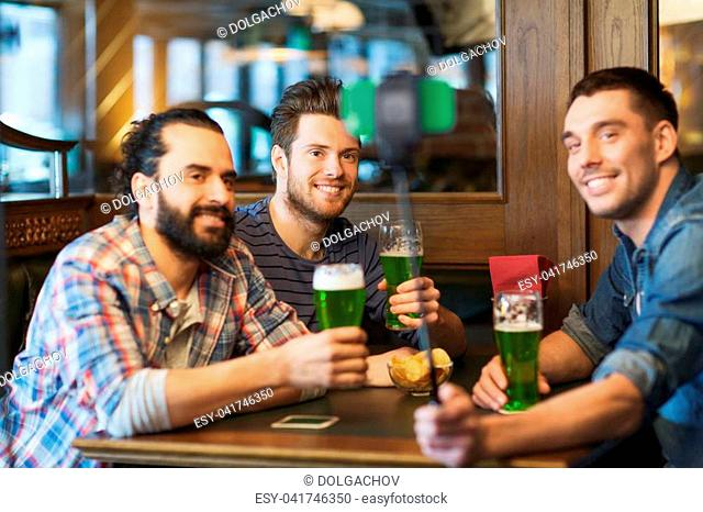 st patricks day, leisure and technology concept - happy male friends drinking green beer and taking picture with smartphone selfie stick at bar or pub