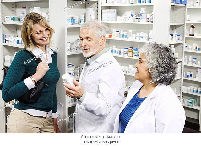 Pharmacists explaining medication to customer