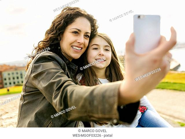 Happy mother and daughter taking a selfie