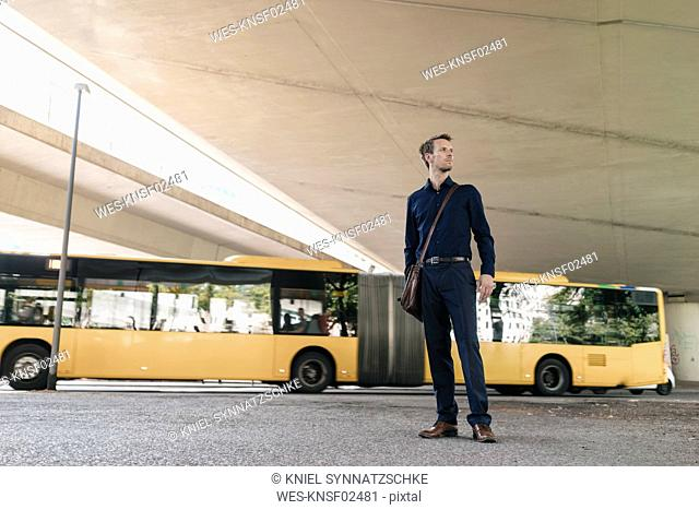 Businessman standing at underpass with bus in background