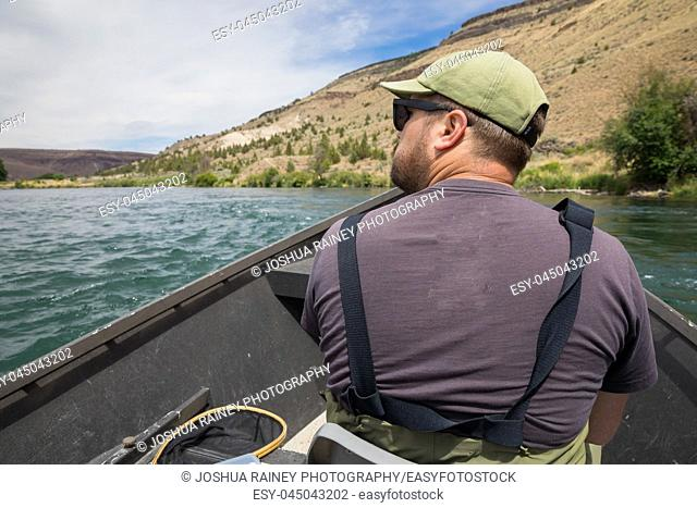 Fly fisherman sitting in a drift boat while floating the river to get to the next fishing access on the Lower Deschutes River near Warm Springs Oregon