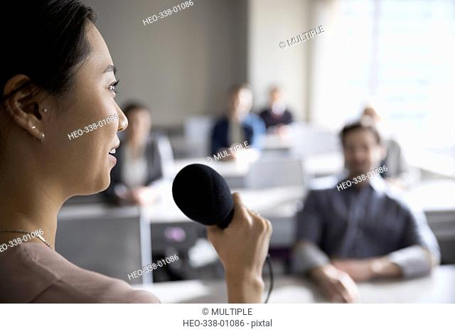 Businesswoman with microphone speaking to business people in classroom