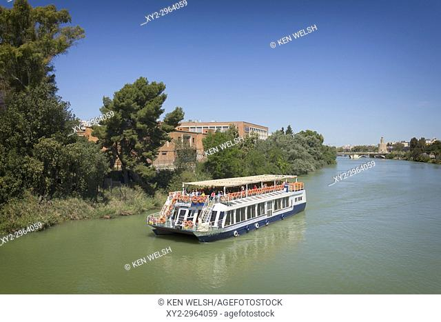 Seville, Seville Province, Andalusia, southern Spain. Pleasure cruise boat on the Guadalquivir river. Torre del Oro (Tower of Gold) in the distance on right