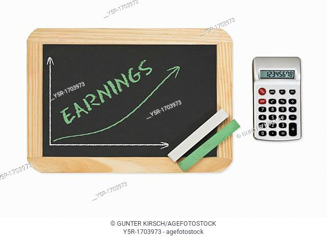 Detail photo of a chalkboard. A chart with an increasing curve on this. On the chalkboard is the word Earnings written. Green and white chalk lies in a corner